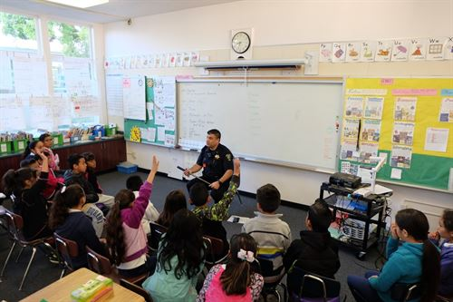 Police officer speaking to students in a classroom during mini-career day.